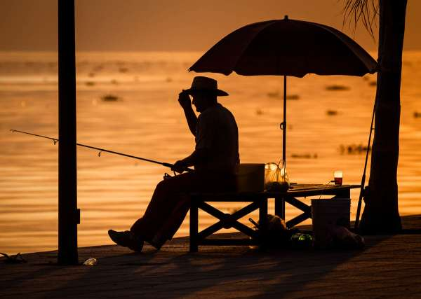 A man adjusts his hat while fishing in the evening on Lake Chapala from the Ajijic malecón (boardwalk).