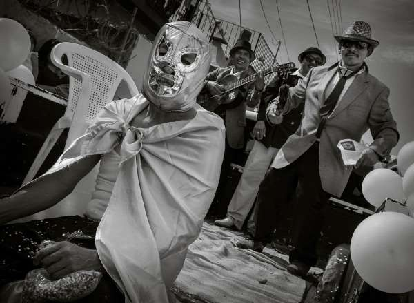 A man in a Mexican wrestling mask sits on the back of a truck during the New Year's Day parade in Ajijic, Jalisco, Mexico.