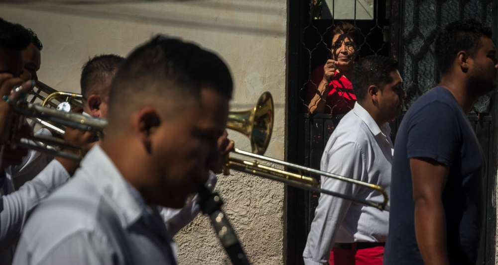 Woman watching a banda go by in a procession in Jalisco.