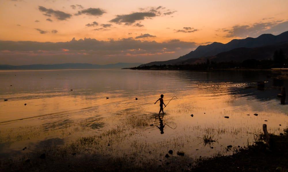 Boy with stick walking on shore of Lake Chapala.