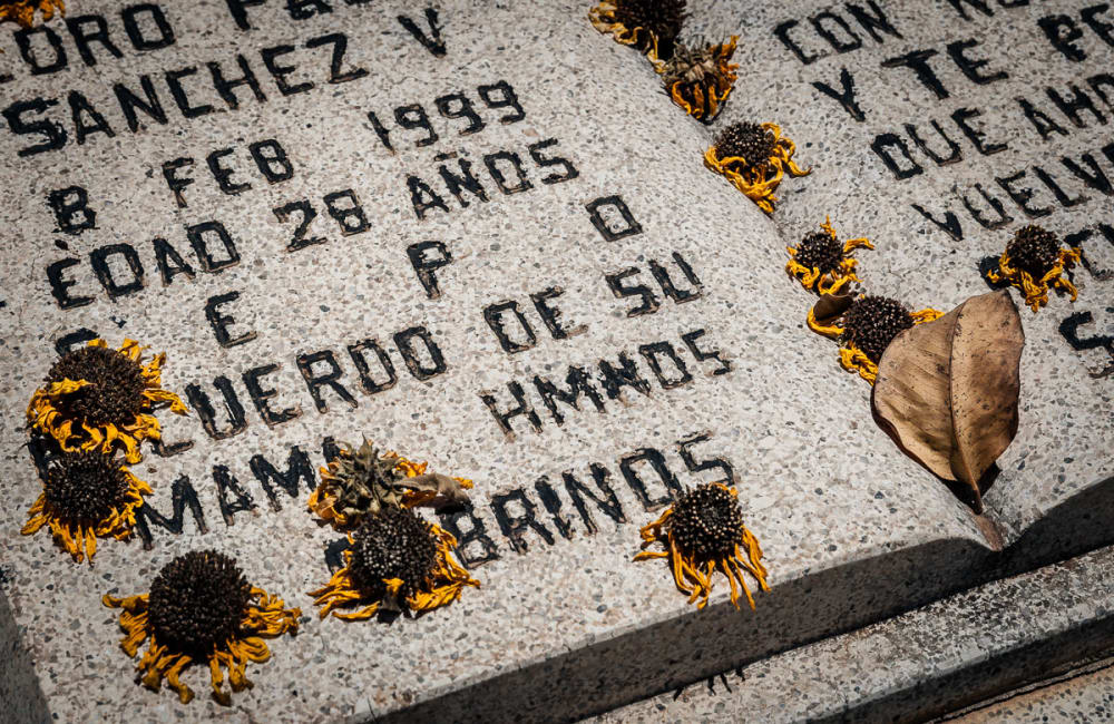 Dried marigolds on a headstone in Los Mochis area cemetery, Sinaloa.