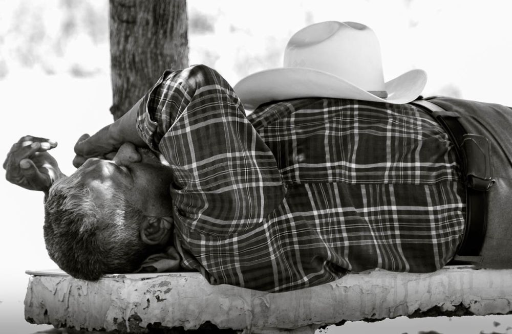 A man takes a siesta on a bench in a cemetery in Sinaloa, Mexico.
