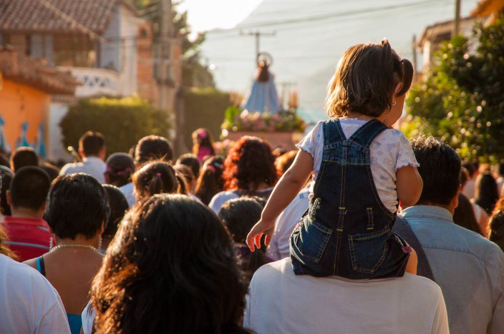 A girl uses some shoulders to get a better view of the procession trailing behind the image of the Virgin of the Rosary.