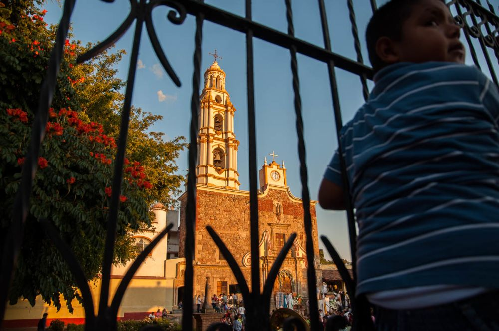 Boy watching fiesta-day mass at San Andrés Church in Ajijic, Jalisco, Mexico