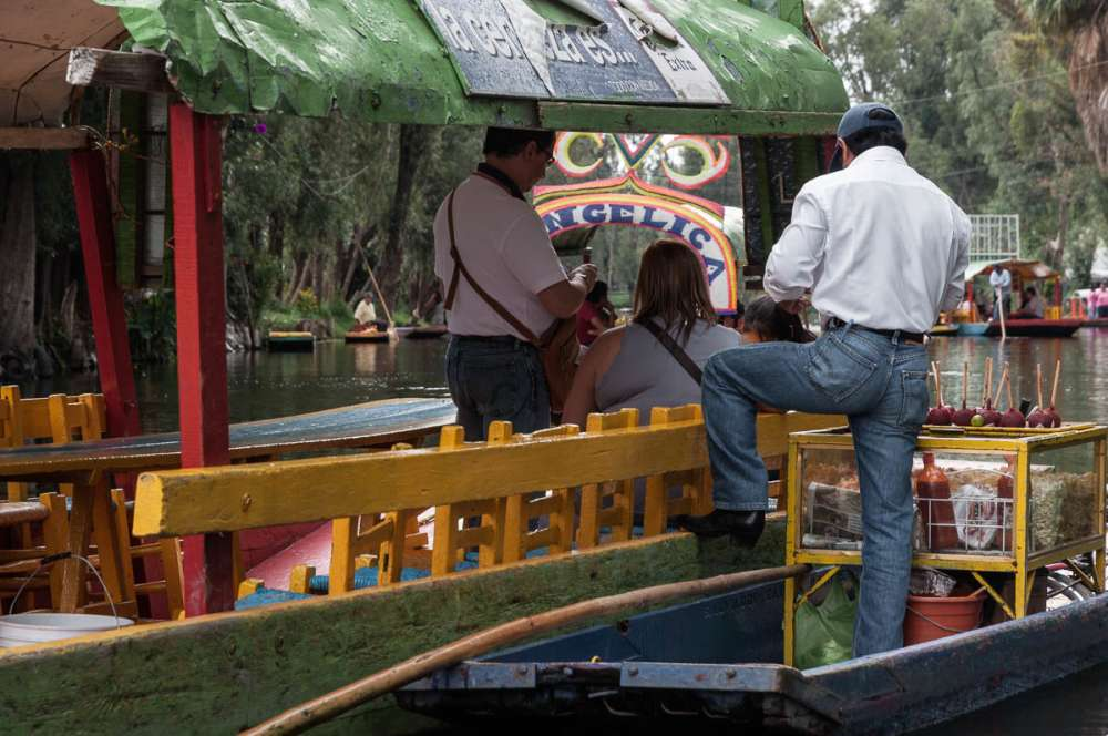 Man selling snacks to visitors at the floating gardens of Xochimilco.