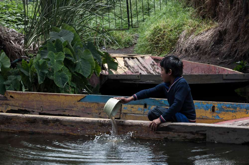 Boy emptying water from his boat at Xochimilco.