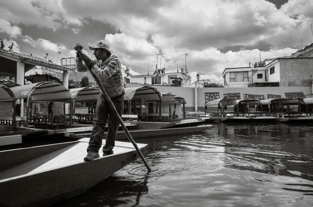 A trajinera operator pushing his boat with a pole at Xochimilco.