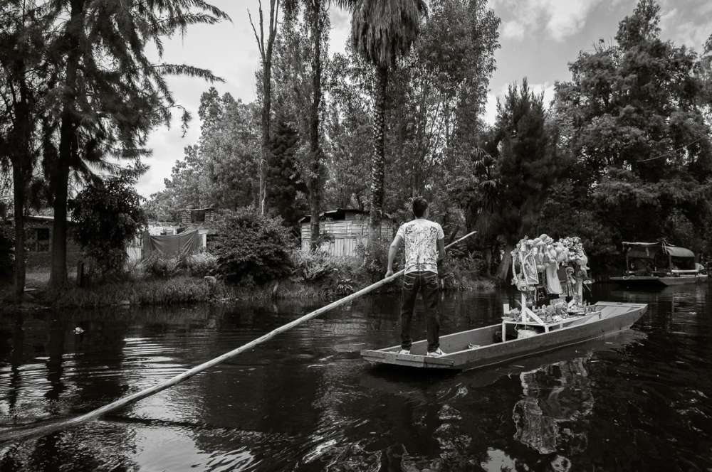 Young man using pole to move his boat through the canals at Xochimilco.