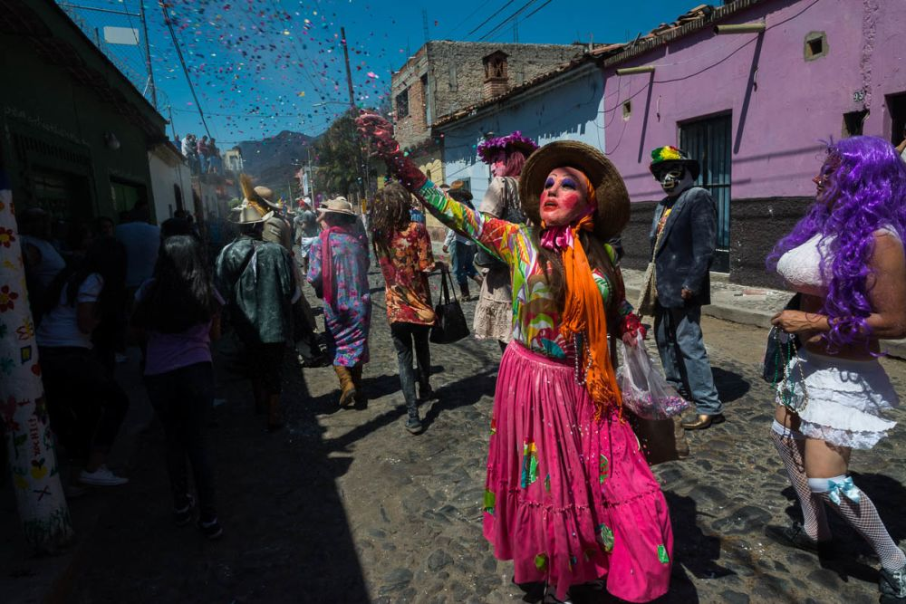 A masked zayaca throws confetti during Carnaval in Ajijic, Mexico.