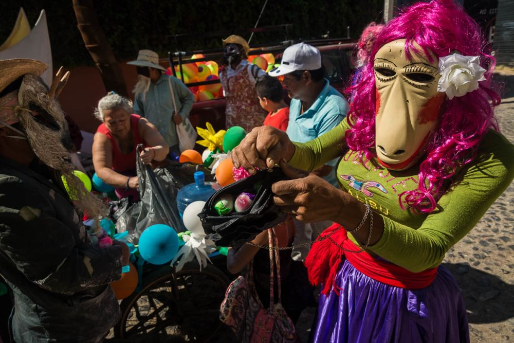A zayaca zips confetti-filled eggs into a handbag before the Carnaval day parade in Ajijic.