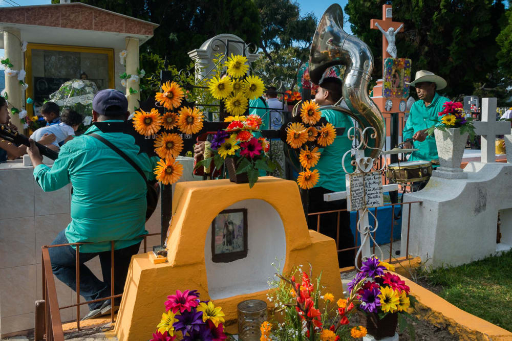 Musicians play for a family mourning during the Day of the Dead in Chapala, Jalisco, Mexico.