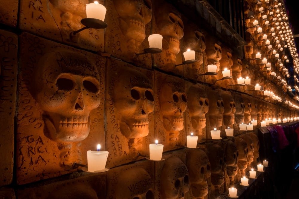 Candles light up a wall of clay skulls on the Day of the Dead in Ajijic.