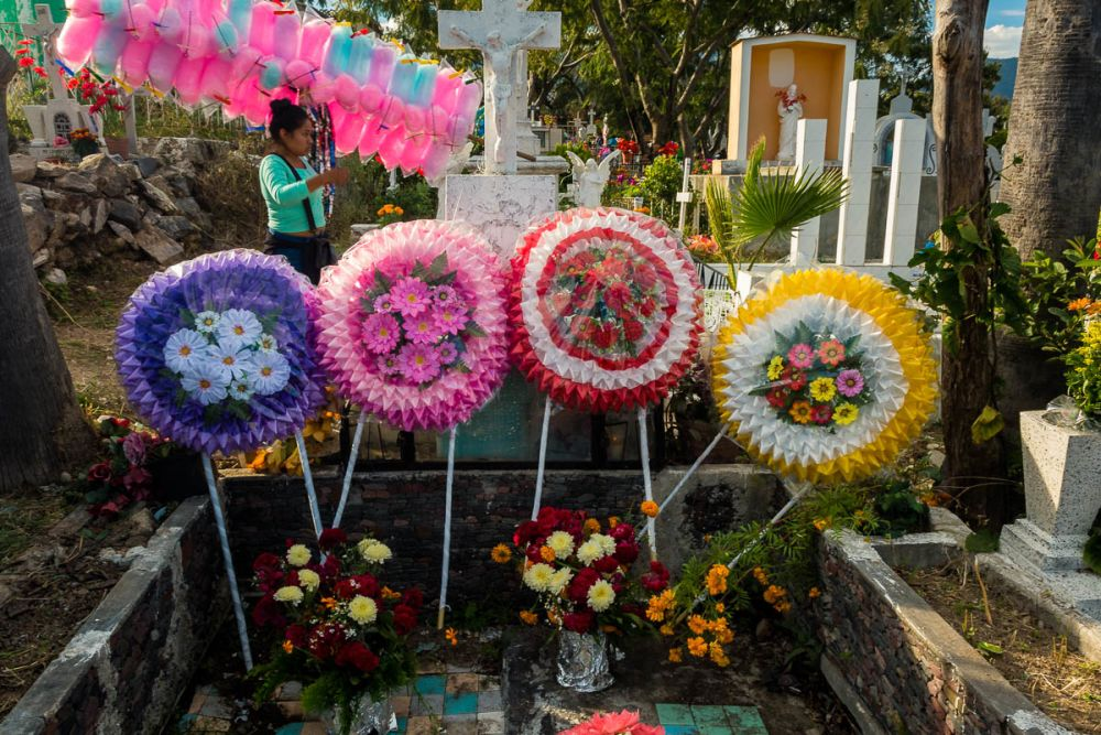 A woman selling cotton candy in the Chapala, Jalisco, graveyard walks by a tomb decorated with coronas on the Day of the Dead