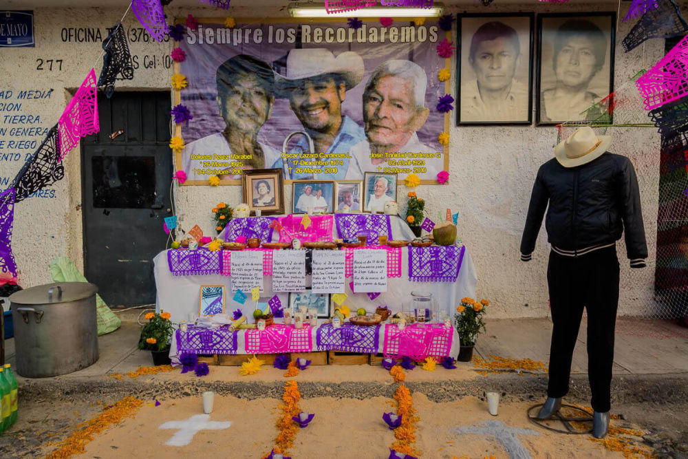 The Day of the Dead altar is built to welcome the dead back for their overnight journey to the living. Families leave offerings such as favorite foods or alcohol, as well as practical comforts such as soap and water, and clothes. For this altar, the family has dressed a mannequin with the deceased clothes and sombrero.