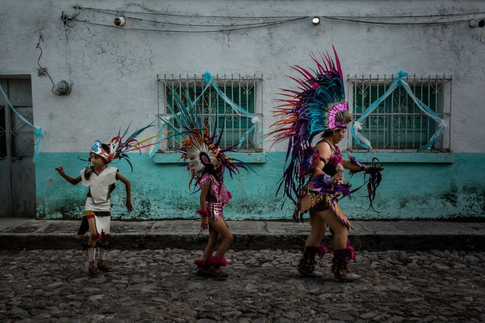 A group of pre-Hispanic dancers takes part in a procession for Our Lady of the Rosary in Ajijic, Jalisco, Mexico. Aztec dancers often form an essential part of important Catholic processions 500 years after the Spanish first arrived to conquer the country.