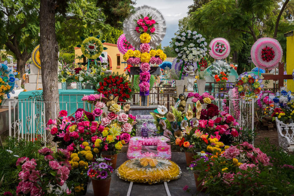 Flower arrangements and coronas line a tomb in the graveyard in San Antonio Tlayacapan.,