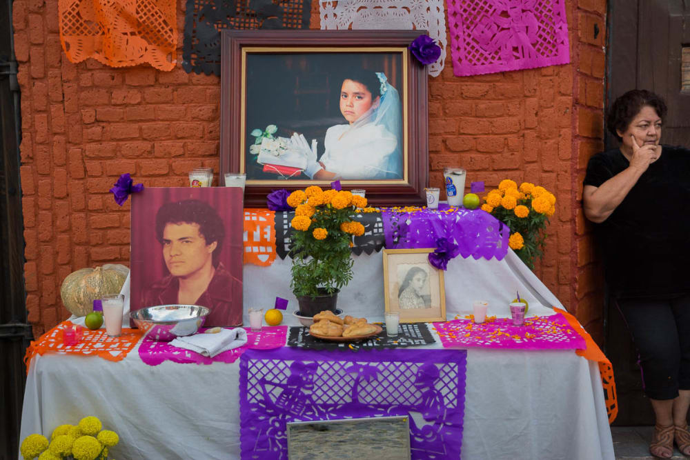 A woman next to a Día de los Muertos altar for her family.
