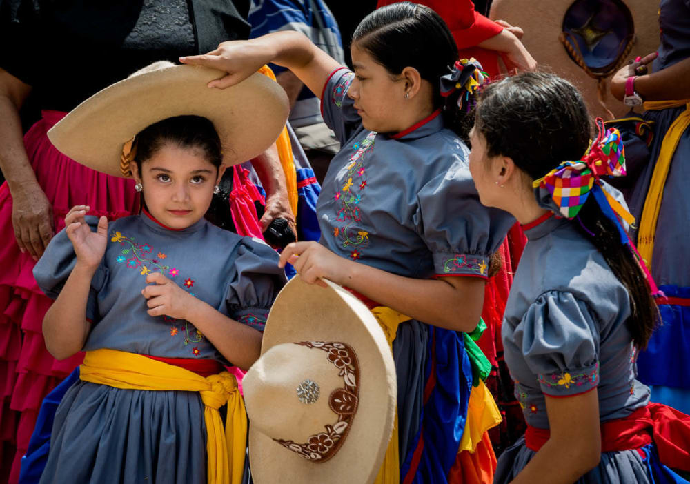 Escaramuza cowgirls helping each other put on their sombreros.