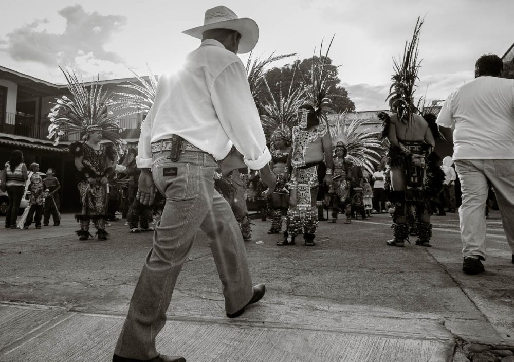 Man walking through Aztec dancers before the procession for Our Lady of the Rosary in Ajijic.