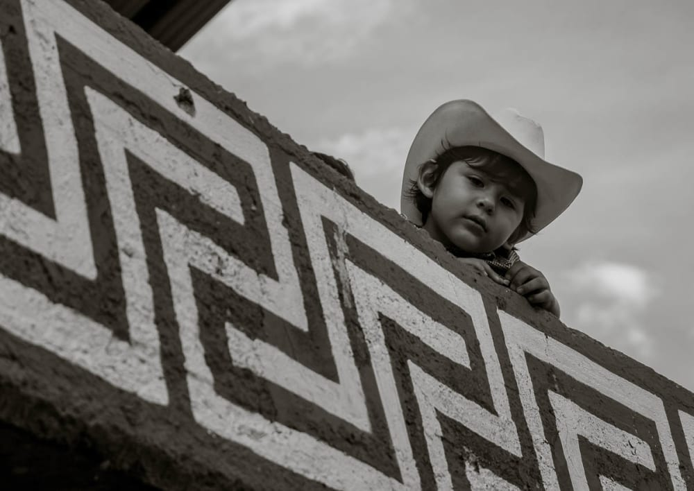 A little cowboy watches the events unfold in the town bullring.