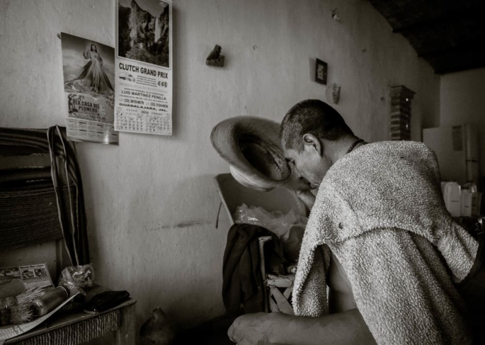 Ismael Sánchez kiss the brim of his hat while saying a prayer after getting home, Ajijic, Jalisco, Mexico.