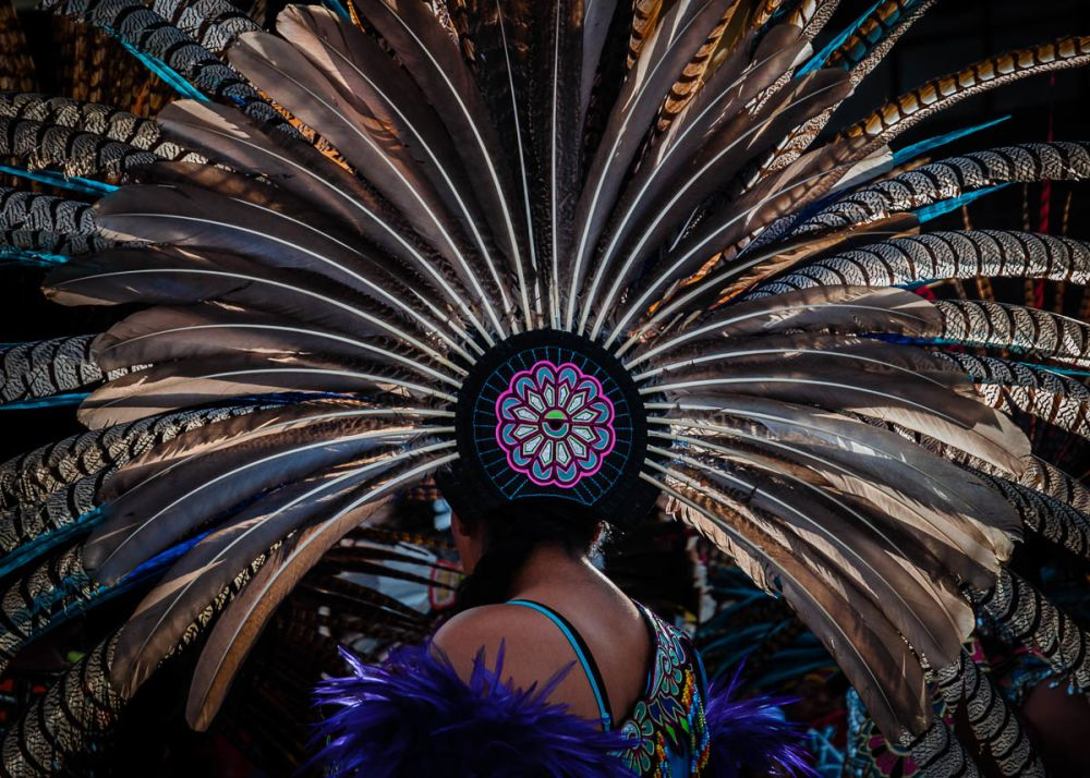 An Aztec dancer wears a large copili headdress made from peacock and turkey feathers during the Fiesta of the Virgin of the Rosary. The Virgin of the Rosary is the town's patroness and has the month of October devoted to her with fireworks, more firework, even more fireworks, and a final procession through bearing an image of the virgin through the town on October 31.