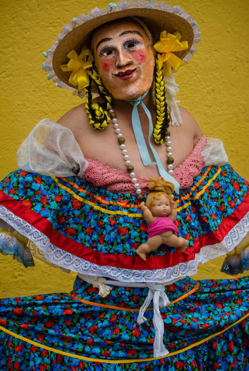 A zayaca wears a dress with a necklace made from a baby doll.