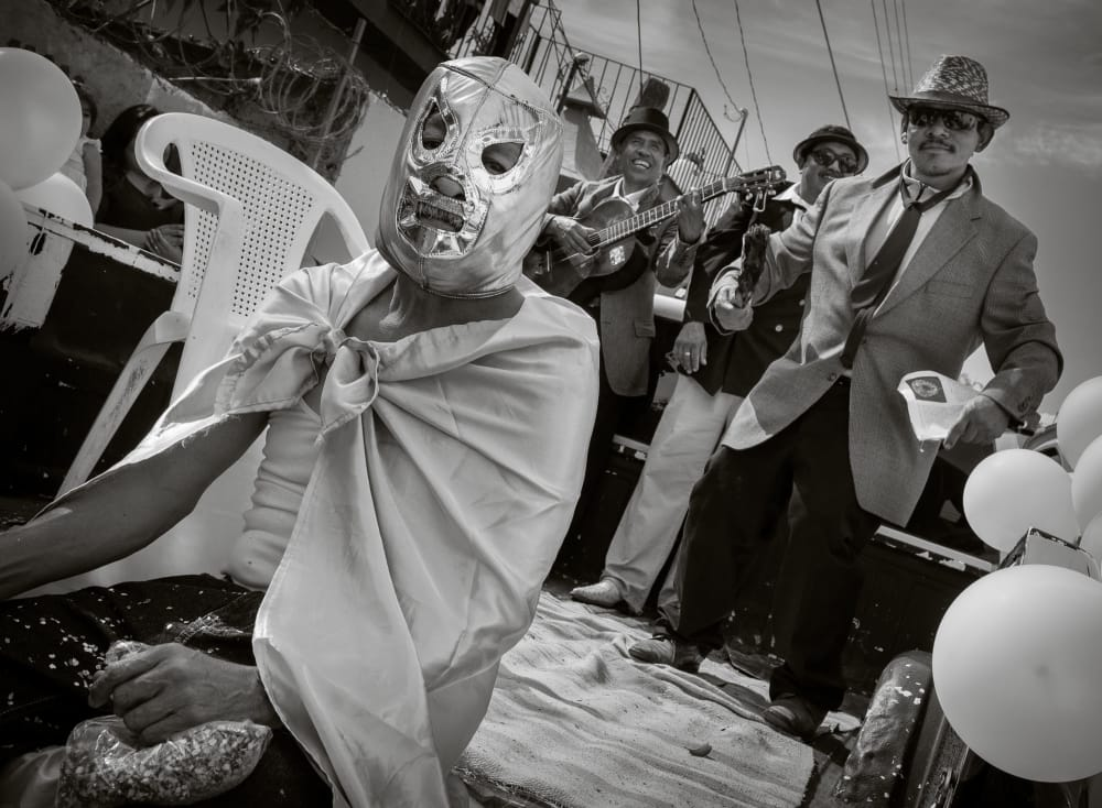 A man wearing a Mexican lucha libre mask sits on the tailgate of a truck as musicians play along to pre-recorded hip hop music during the 2015 New Year's Day Parade in Ajijic, Jalisco, Mexico