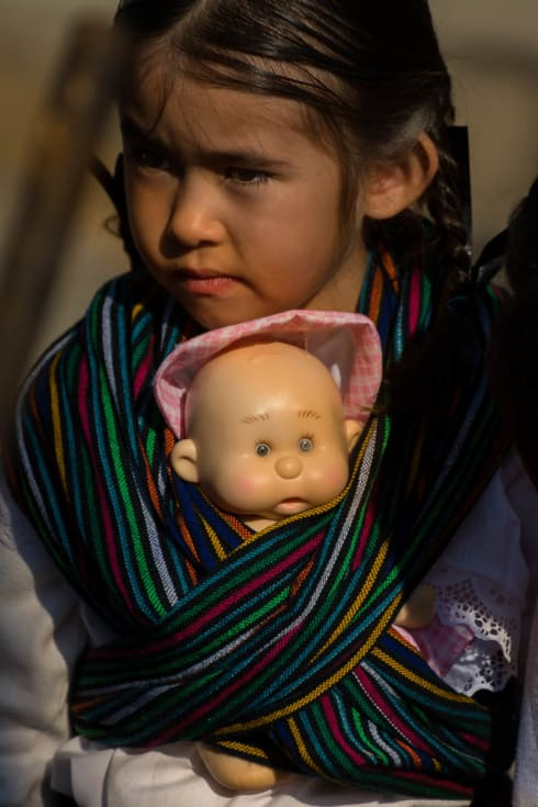 Girls sometimes march with a baby doll wrapped in a rebozo.