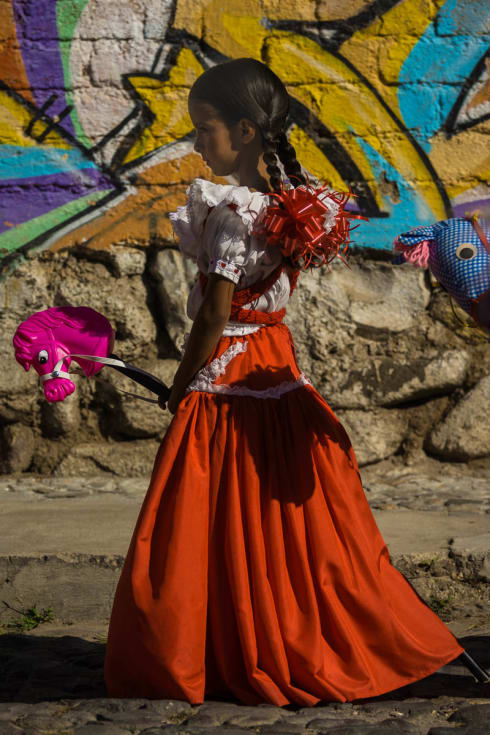 An adelita with a toy horse takes part in the Revolution Day parade in Ajijic, Jalisco, Mexico.