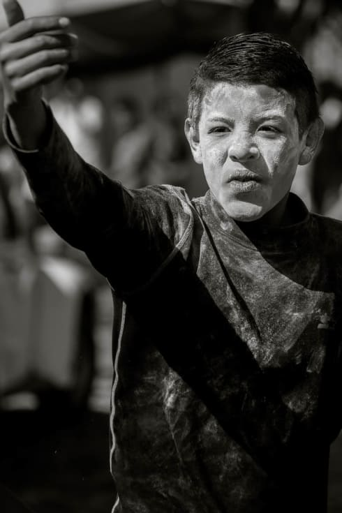 A boy taunts a group of zayacas during the Carnival fiestas in Ajijic, Mexico.
