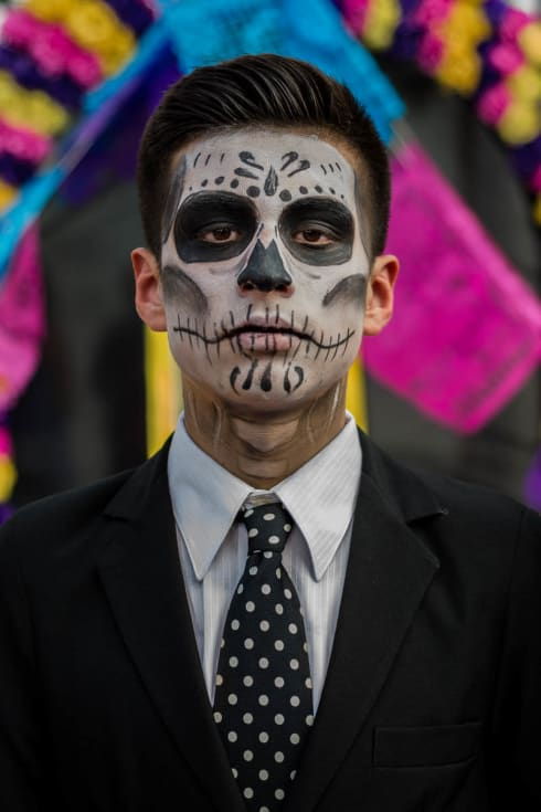 A young man dressed as a catrine on the Day of the Dead in Chapala, Jalisco. The catrina (feminine) or catrine has been a part of the Day of the Dead traditions since Mexican printmaker José Guadalupe Posada created his 1910 etching La Calavera Catrina. The etching of a skeleton sporting elegant dress the catrina is not only an iconic part of the Day of the Dead, but one of Mexico's most identifying aspects.