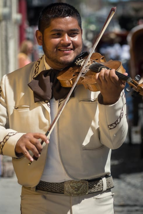 A violinist in a mariachi group performing for a quinceañera.