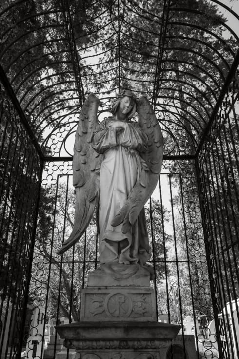 A statue of a stone angel inside a cage in the Panteón Municipal in Morelia, Michocacán.