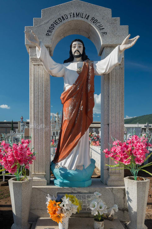 A status of Jesus with outstretched arms in the cemetery in Atotonilquillo, Jalisco.