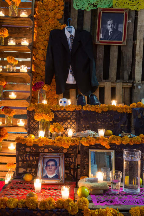 Candles on a Day of the Dead altar for Humphrey Bogart and Santo Toribio Romo.
