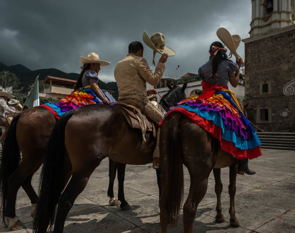 Cowboys and escaramuza cowgirls wait outside a church for a mass to end.