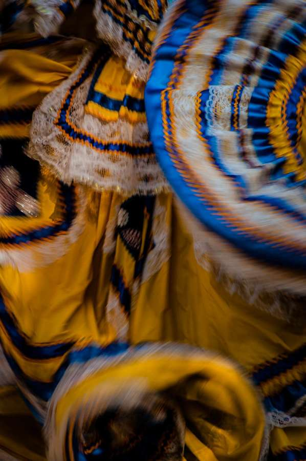 The dress of a Mexican ballet folklórico dancer blurs together during a performance in Jalisco, Mexico. Mexico has dozens of regional folk dances which have survived since their pre-Hispanic origin and today they're performed by dedicated dancers who are conscious of preserving the traditions which are in danger of being lost to modernity. The dress in this photo is a style typical from the region of Jalisco.