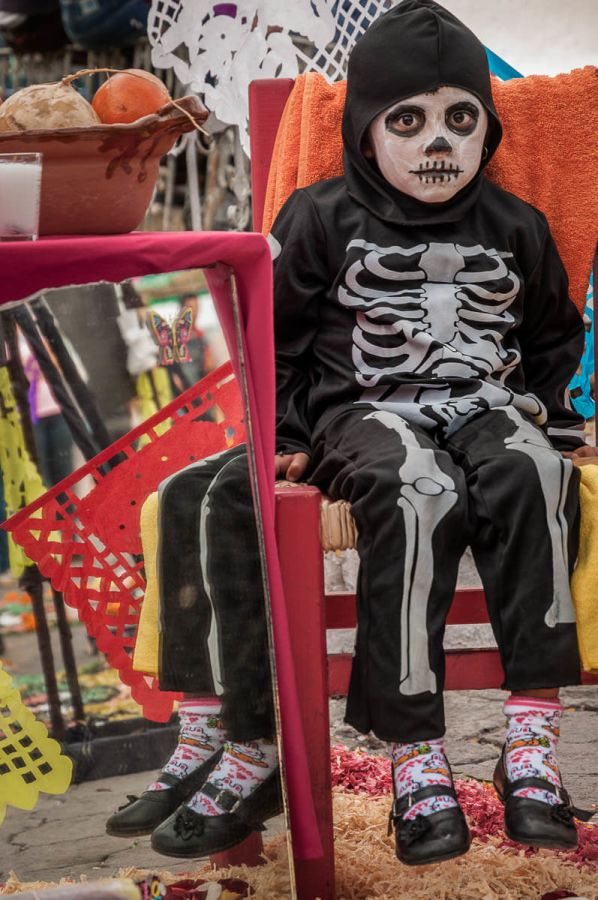 A girl sits as a catrina next to a mirror, a traditional component of the Day of the Dead altar so the spirits can check their appearance upon arrival.