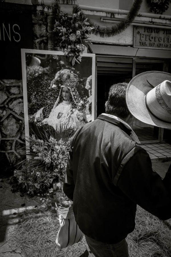 Man lifting his hat while passing image of La Virgen de la Merced in San Cristóbal de las Casas