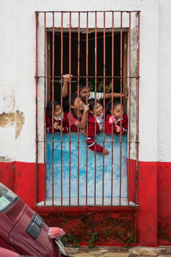 """Schoolkids wait for the """"Parade of the Fatties"""" (la Fiesta de los Panzones) in San Cristobal de las Casas, Chiapas, Mexico"""