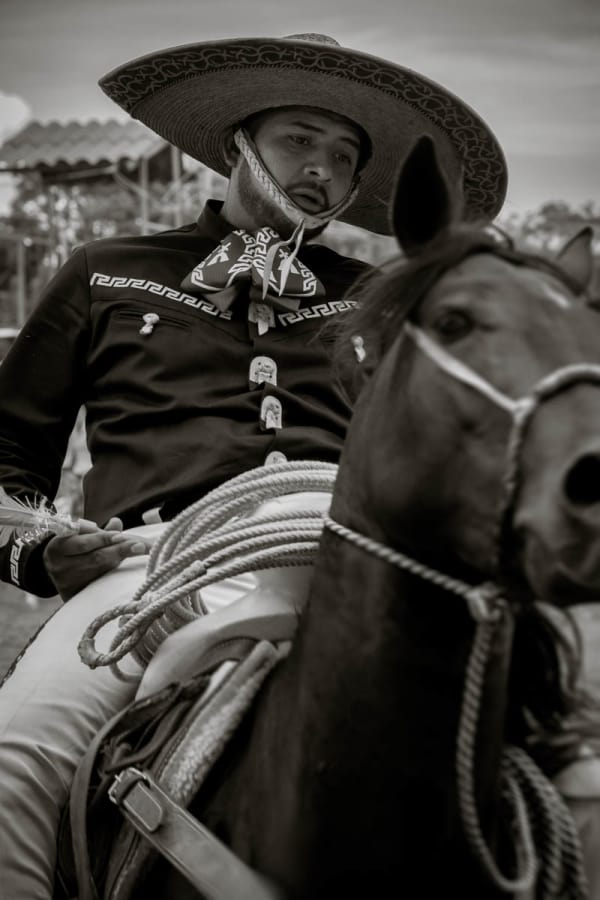 A cowboy plays a game of darts on horseback during el Diá del Charro.