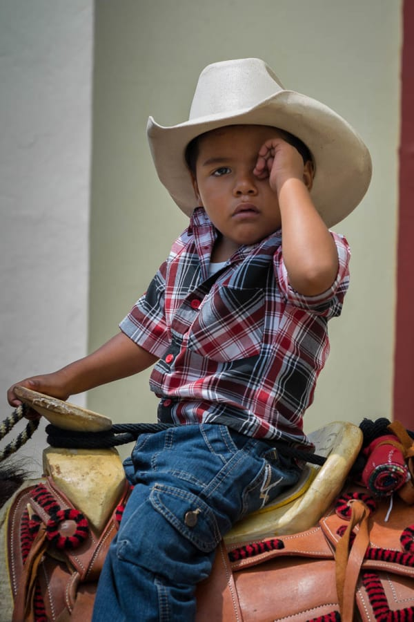 A young cowboy wipes the sleep from his eyes while waiting for mass to end on the Day of the Cowboy.