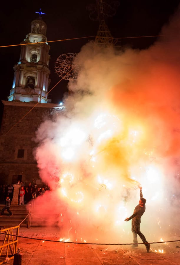 A worker helps a fireworks castle to get moving during the fiestas patronales in Ajijic, Mexico.