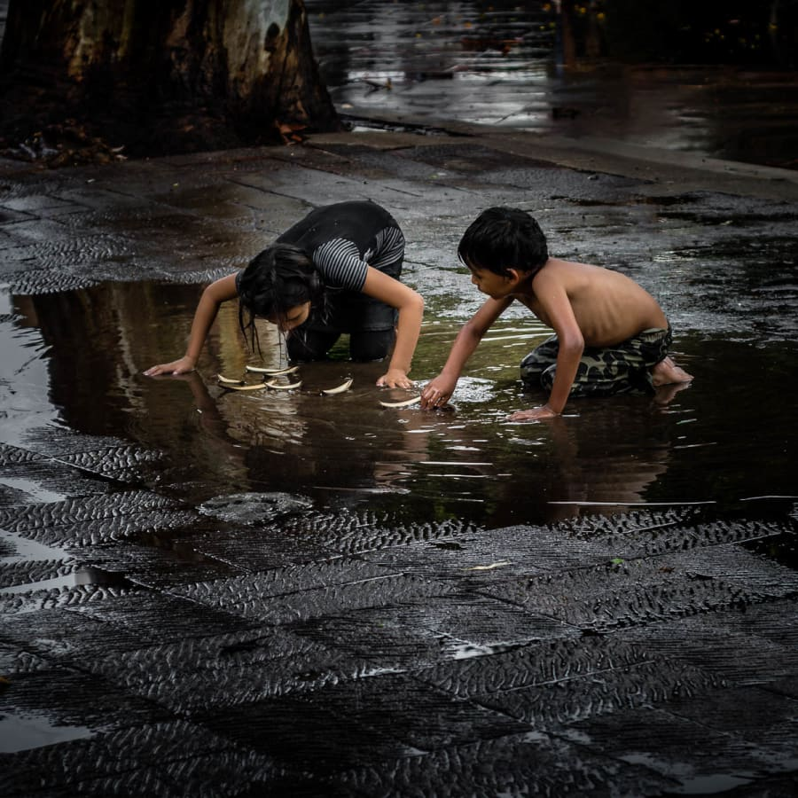 A brother and sister improvise and play in a puddle with boats they made out of fallen leaves after a brief afternoon thunderstorm hit the plaza in Ajijic, Mexico. One of the qualities that separate many kids who live in a place like the United States from, say, a place like Mexico is the ability, and at times the necessity, of creating games out of practical everyday items or found objects, such as pesos, rocks or these leaf boats, as shown in the photo.