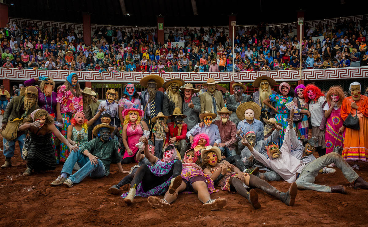The zayacos gather in the packed bullring with their town behind them in the stands.