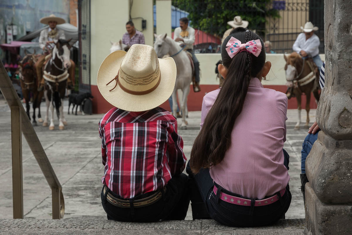 Kids watching cowboys in the church courtyard.