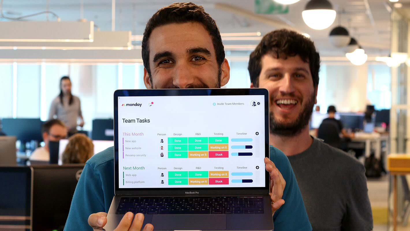 Two happy software engineers showing their board