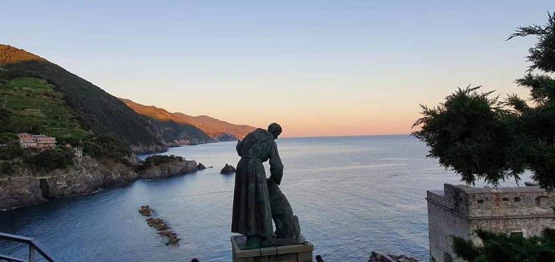 statue of bendetto d'assisi with the sea in the background