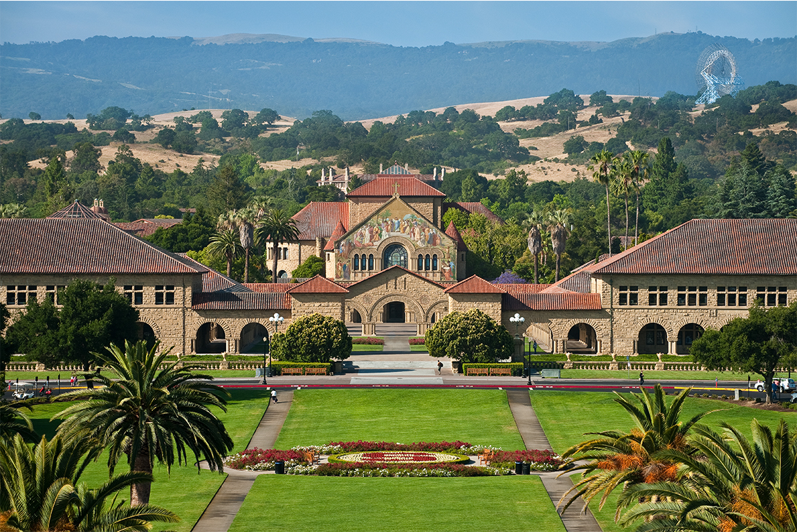 Aerial view of main Stanford campus with foothills and the Dish in the background.